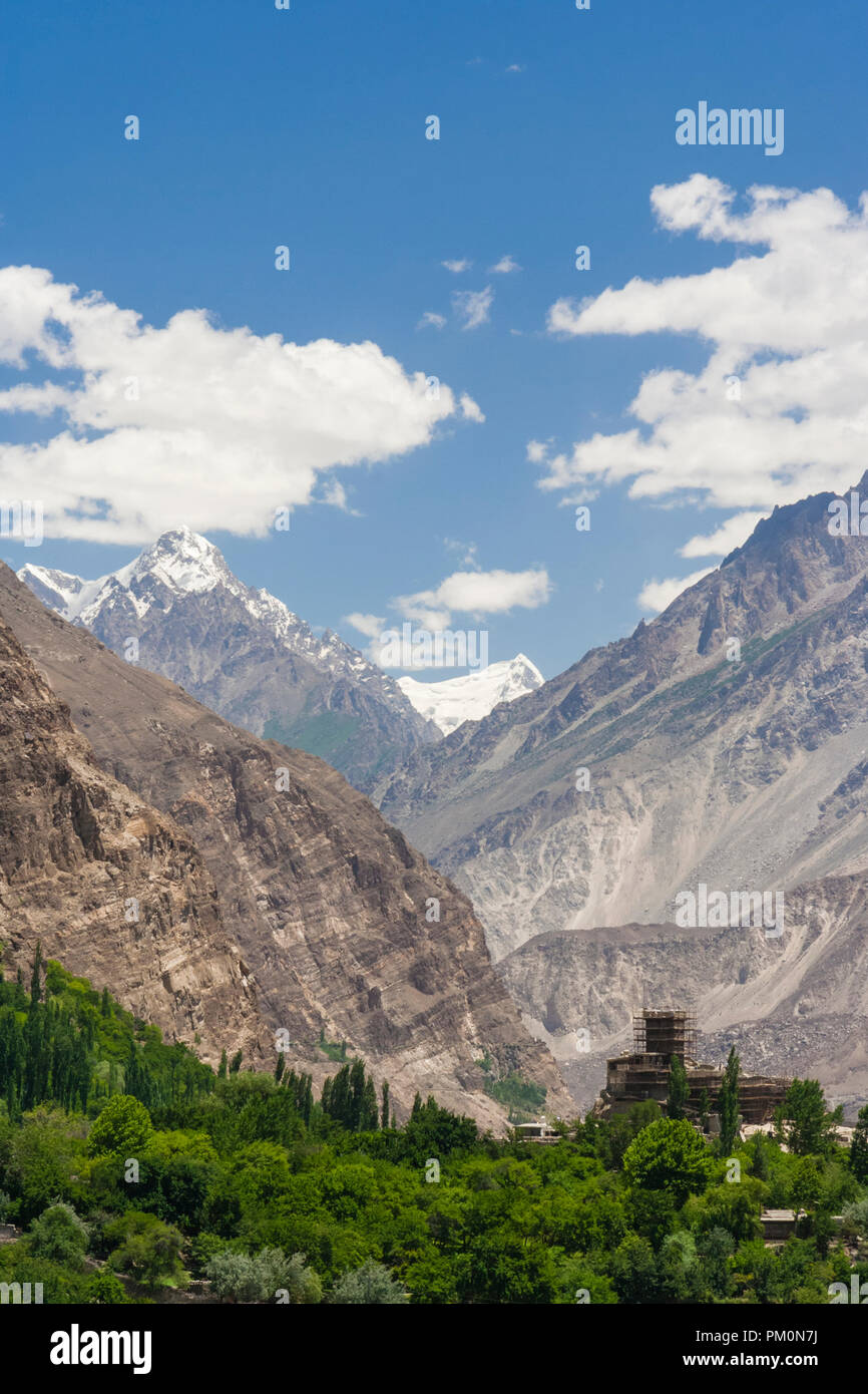 Altit, Hunza Valley, Gilgit-Baltistan, Pakistan : Karakoram mountains dwarfing Altit Fort. Founded on 11th century the fortress was home during three  - Stock Image