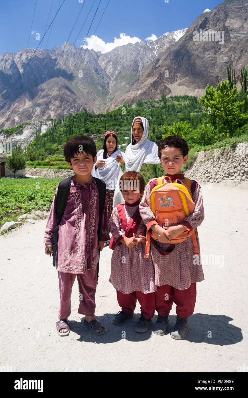 Karimabad, Hunza Valley, Gilgit-Baltistan, Pakistan : Two women and three school children on their way home pose for a portrait on the road from Altit Stock Photo
