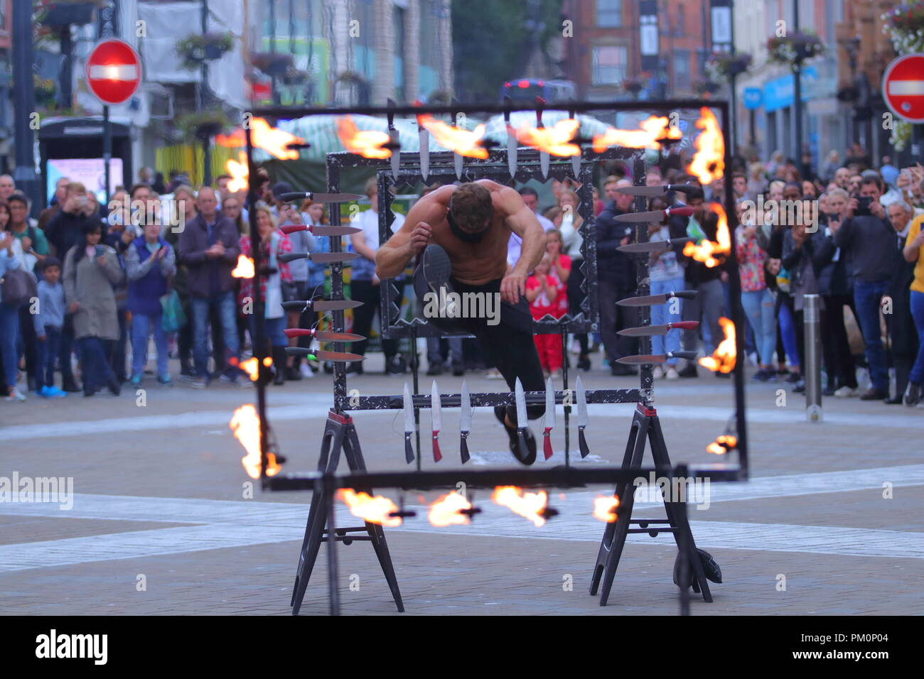 A dare devil throws his self through sharp knives & fire while  blindfolded as part of his street theatre act on Briggate, Leeds,West Yorkshire. - Stock Image