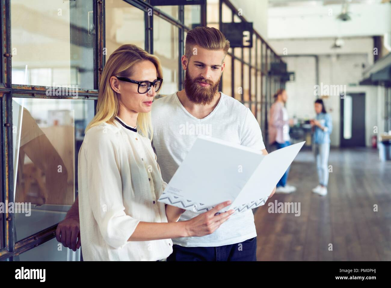 Sharing fresh ideas. Group of young business people in smart casual wear talking and smiling while standing in the office hallway. - Stock Image