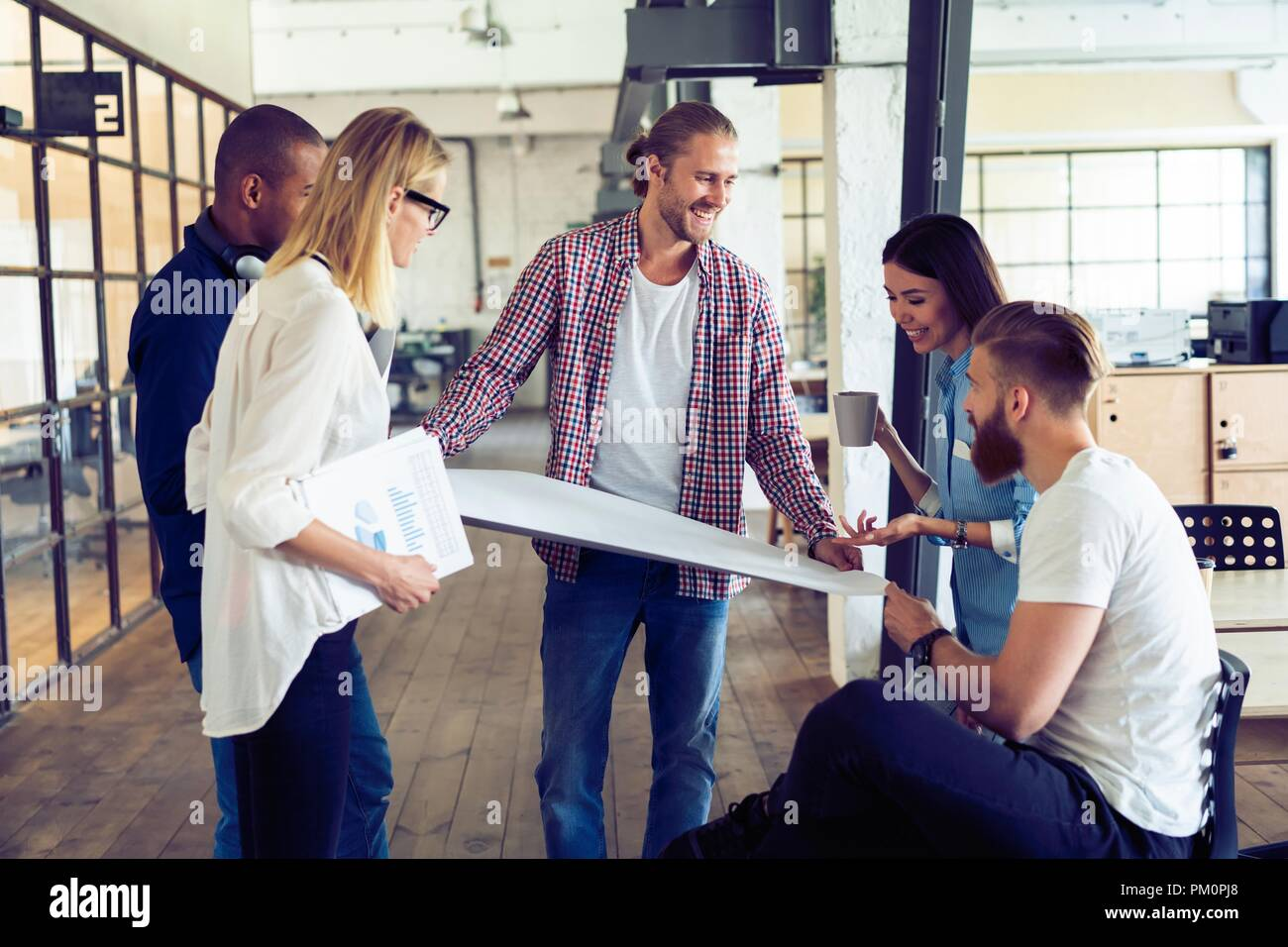 Working as a team. Full length of young modern people in smart casual wear planning business strategy while young woman pointing at large paper in the office hallway. - Stock Image