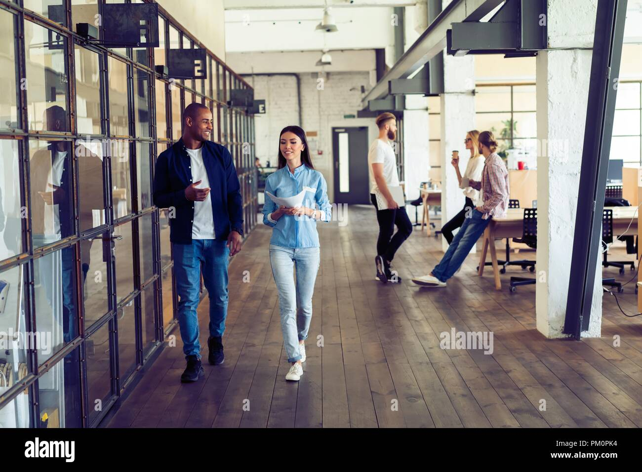 Catching up before meeting. Full length of young modern people in smart casual wear discussing business and smiling while walking through the office corridor. - Stock Image