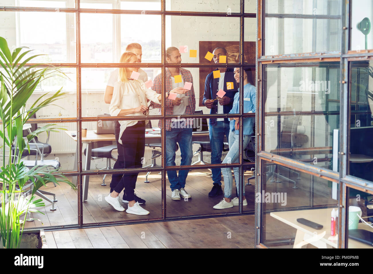 Sharing business ideas. Full length of young modern people in smart casual wear using adhesive notes while standing behind the glass wall in the board room. - Stock Image