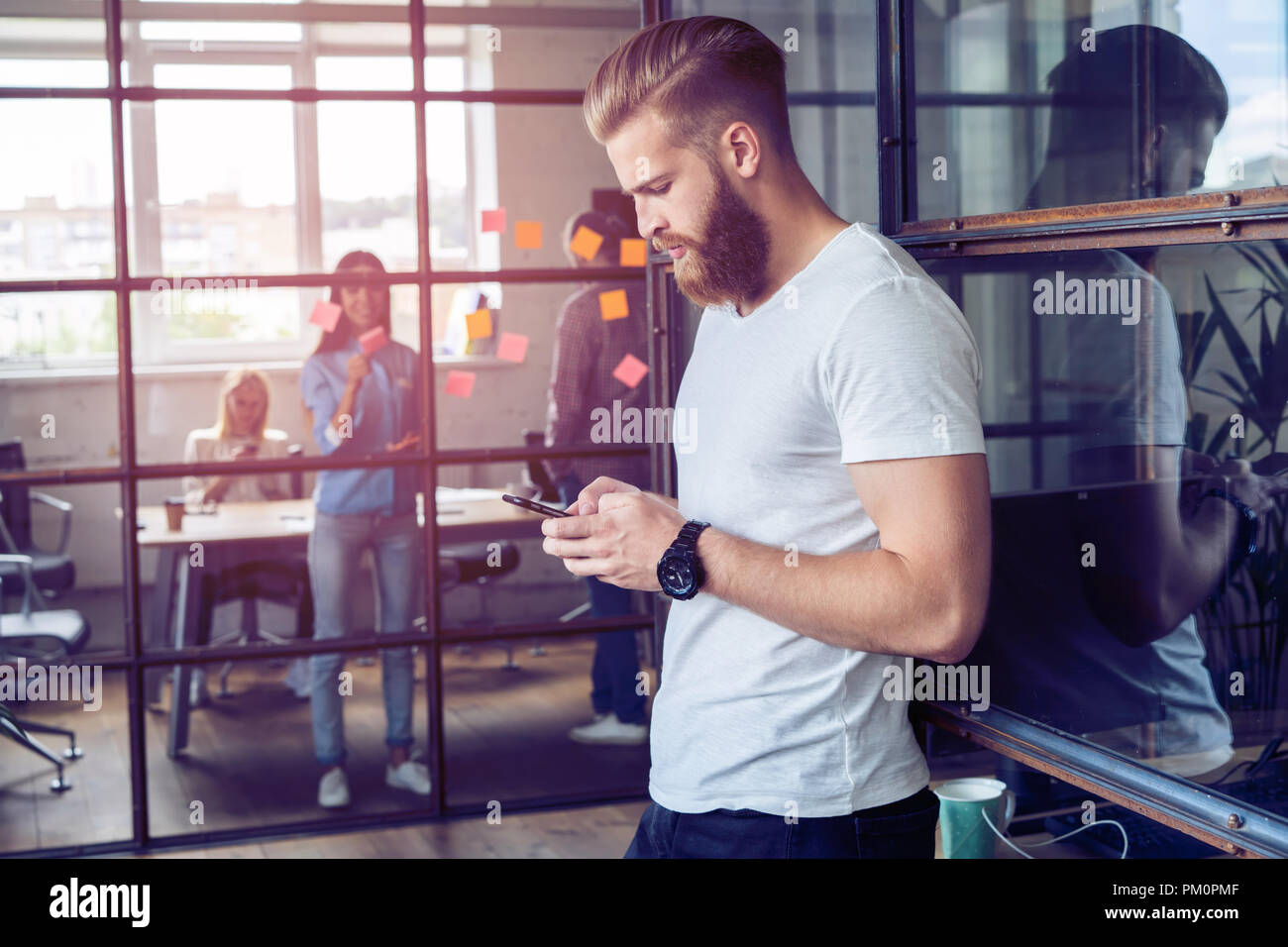 Great message! Handsome young man using his smartphone with smile while standing in his office. - Stock Image