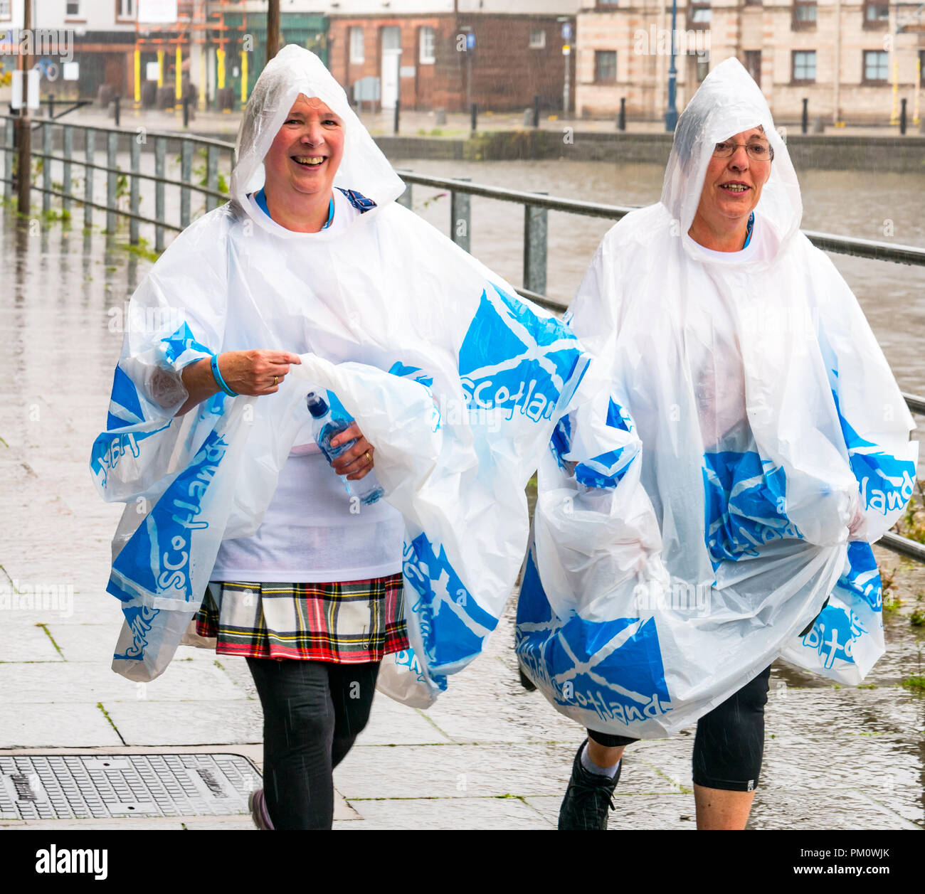 Leith, Edinburgh, Scotland, UK, 16th September 2018. Edinburgh Kilt Walk, the last of four kilt walks this year after those in Glasgow, Aberdeen and Dundee, sponsored by the Royal Bank of Scotland, takes place today. Walkers raise funds for a charity of their choice. There are three walk lengths: the full 24 miles from Holyrood Park to BT Murrayfield Stadium and two shorter walks of 15.5 and 5 miles. The kilt walkers reach The Shore at about Mile 14 in the rain. Two women wearing matching rain ponchos with saltires walk along the riverbank - Stock Image