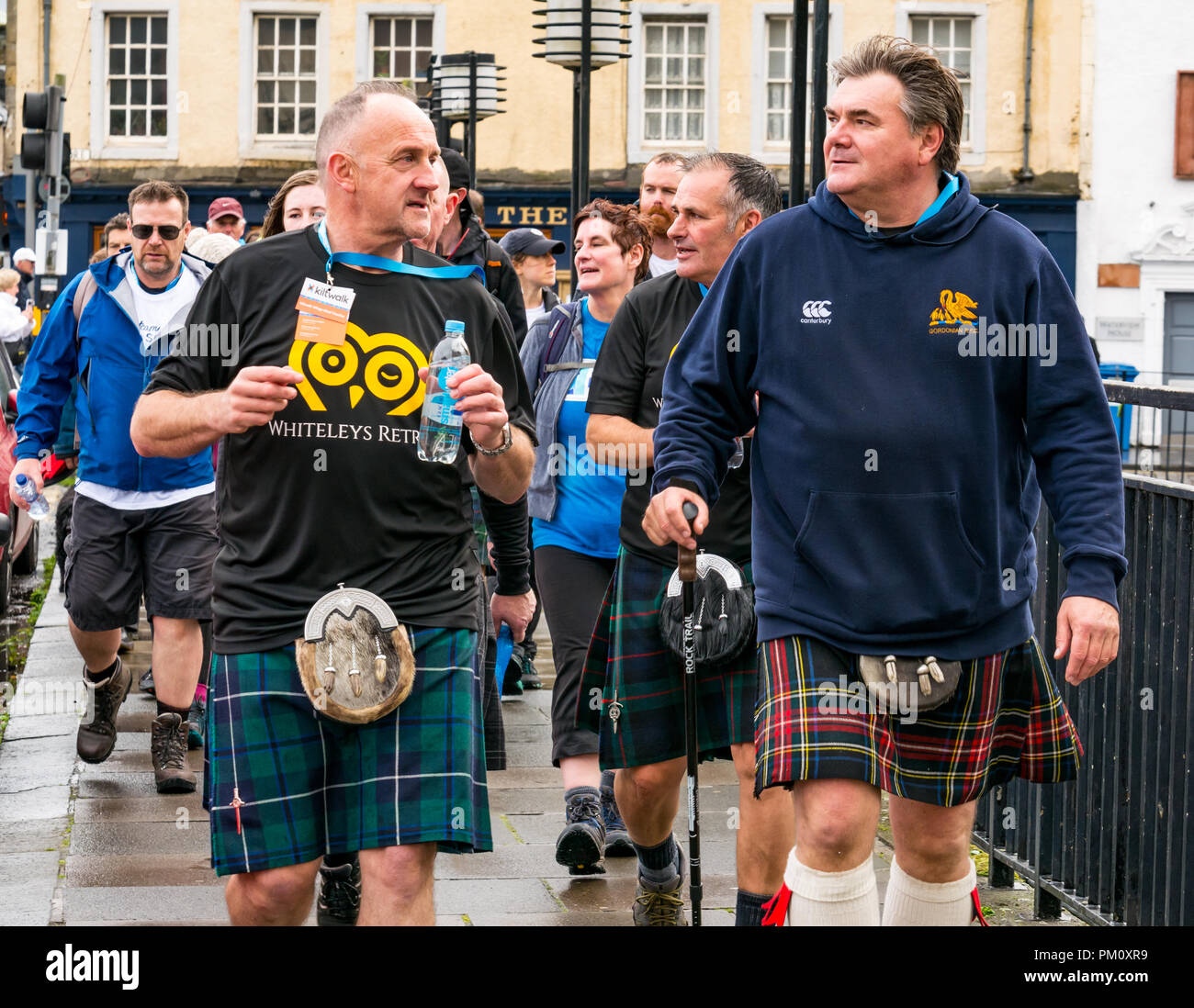 Leith, Edinburgh, Scotland, UK, 16th September 2018. Edinburgh Kilt Walk, the last of four kilt walks this year after those in Glasgow, Aberdeen and Dundee, sponsored by the Royal Bank of Scotland, takes place today. Walkers raise funds for a charity of their choice. There are three walk lengths: the full 24 miles from Holyrood Park to BT Murrayfield Stadium and two shorter walks of 15.5 and 5 miles. The kilt walkers reach The Shore in Leith at about Mile 14. A group of older men wearing kilts walk across the bridge raising money for Whiteley's Retreat - Stock Image