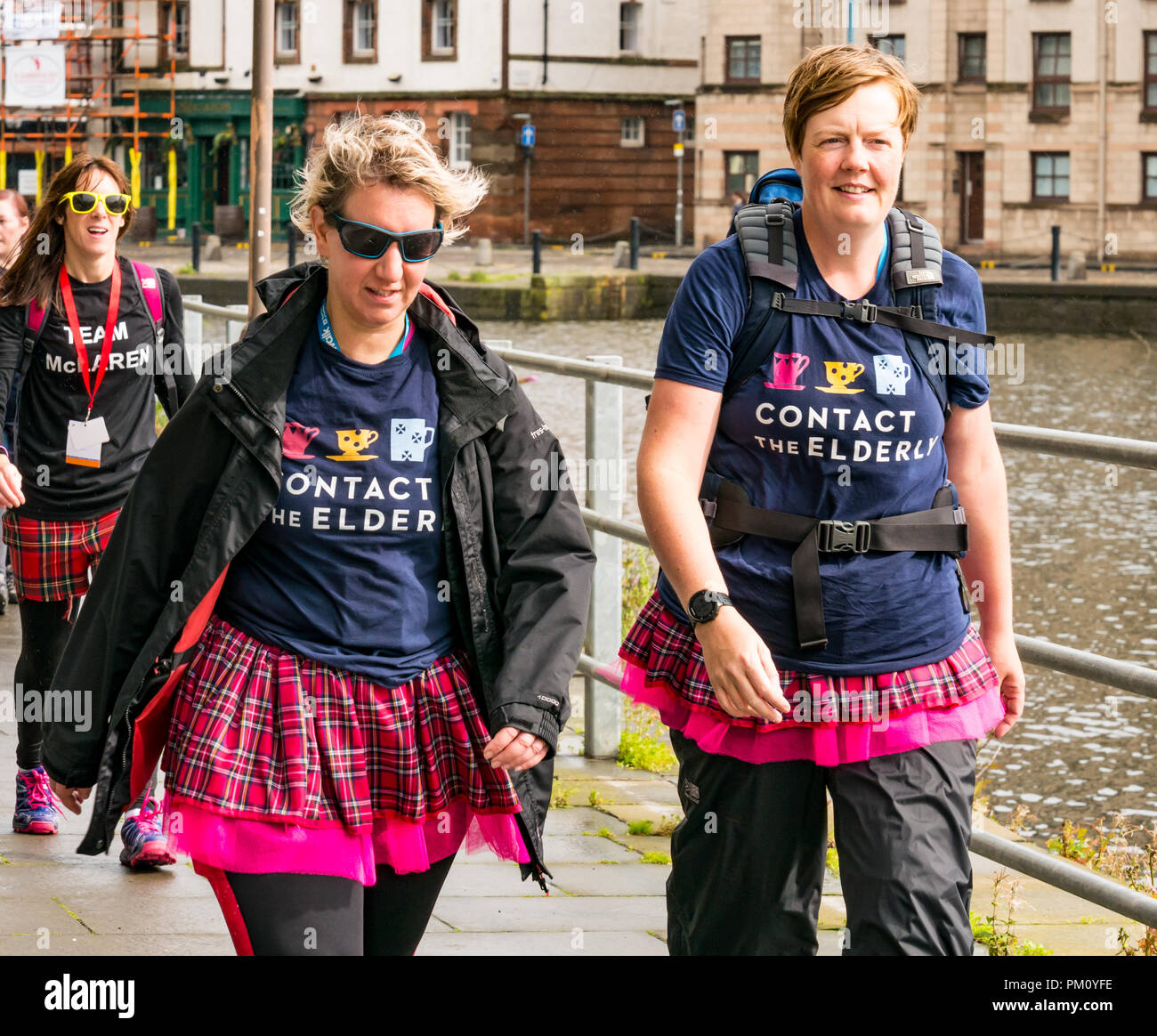 Leith, Edinburgh, Scotland, UK, 16th September 2018. Edinburgh Kilt Walk, the last of four kilt walks this year after those in Glasgow, Aberdeen and Dundee, sponsored by the Royal Bank of Scotland, takes place today. Walkers raise funds for a charity of their choice. There are three walk lengths: the full 24 miles from Holyrood Park to BT Murrayfield Stadium and two shorter walks of 15.5 and 5 miles. The kilt walkers reach The Shore in Leith at about Mile 14. Women in costumed kilts walk along the riverbank raising money for a charity called Contact the Elderly - Stock Image