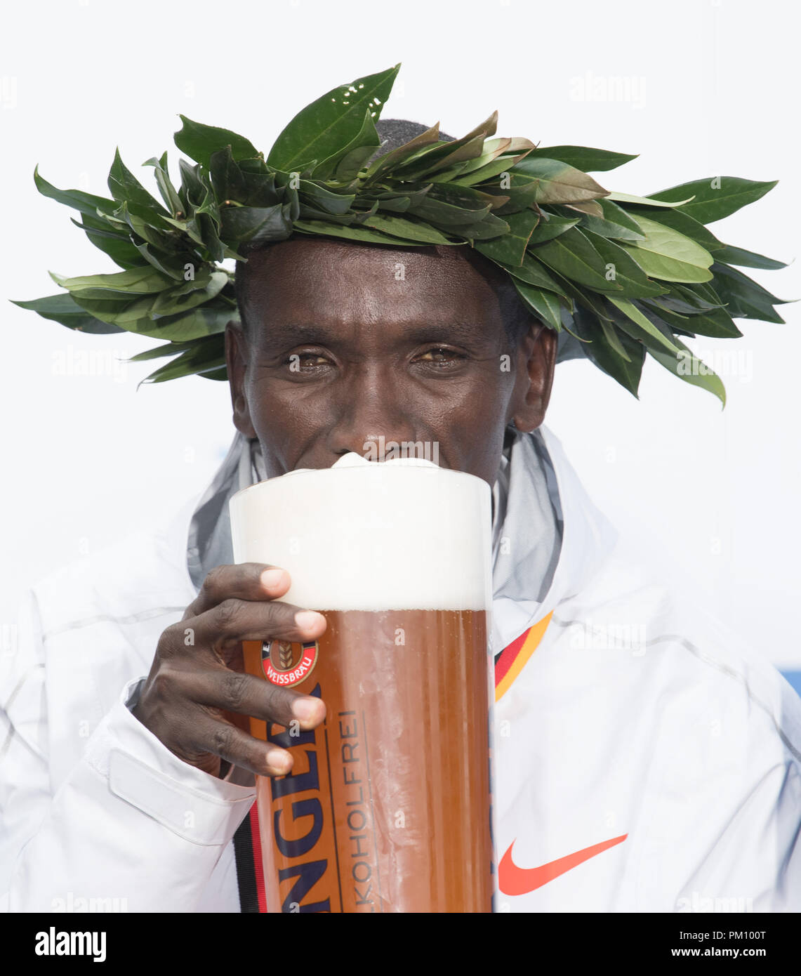 Berlin, Germany. 16 September 2018, Berlin: Kenyan Eliud Kipchoge pleased about his victory in world record time of 2:01:39 during the award ceremony of the 45th BMW Berlin Marathon and holding a glass of Erdinger non-alcoholic beer to his lips. Photo: Soeren Stache/dpa Credit: dpa picture alliance/Alamy Live News - Stock Image