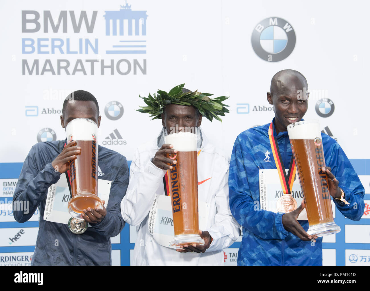 Berlin, Germany. 16 September 2018, Berlin: Kenyan Eliud Kipchoge pleased about his victory in world record time of 2:01:39 during the award ceremony of the 45th BMW Berlin Marathon. Second placed Conseslus Kipruto (L) and bronze medal winner Wilson Kipsang (both Kenyan) stand next to him. Photo: Soeren Stache/dpa Credit: dpa picture alliance/Alamy Live News - Stock Image