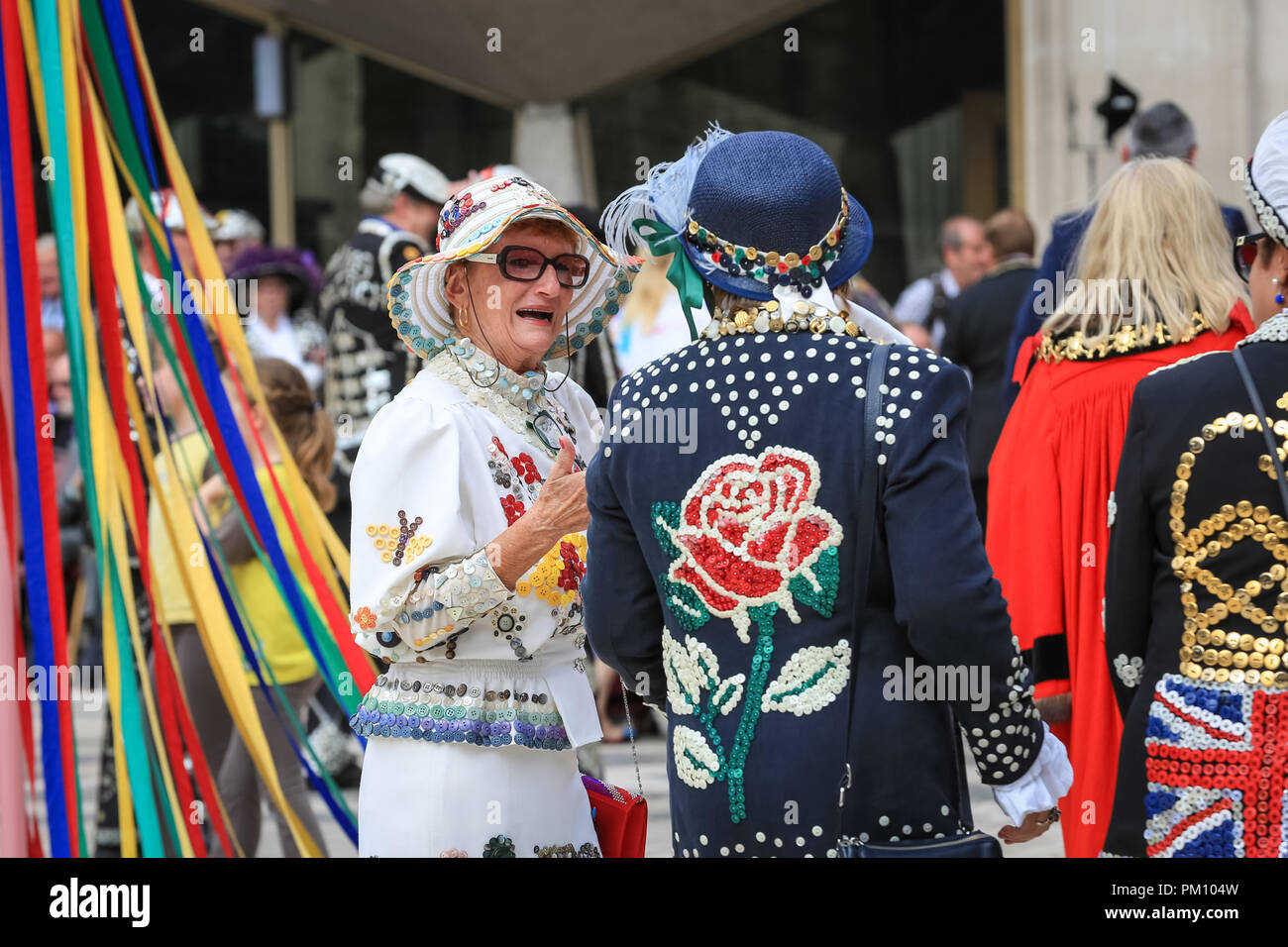 Guildhall Yard, London, UK, 16th Sep 2018. The 20th anniversary of the annual Pearly Kings and Queens Harvest Festival sees the pearlies in their traditional pearl button covered suits and dresses celebrating with Morris dancing, maypole dancing, the Mayors of London and marching bands at Guildhall Yard, before parading through the City of London to St Mary Le Bow Church for a service of thanksgiving. Credit: Imageplotter News and Sports/Alamy Live News - Stock Image