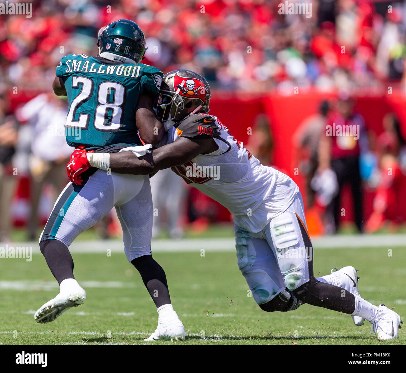 Tampa, Florida, USA. 16th Sep, 2018. Tampa Bay Buccaneers defensive end Jason Pierre-Paul (90) tackles Philadelphia Eagles running back Wendell Smallwood (28) in the 1st half during the game between the Philadelphia Eagles and the Tampa Bay Buccaneers at Raymond James Stadium in Tampa, Florida. Del Mecum/CSM/Alamy Live News - Stock Image