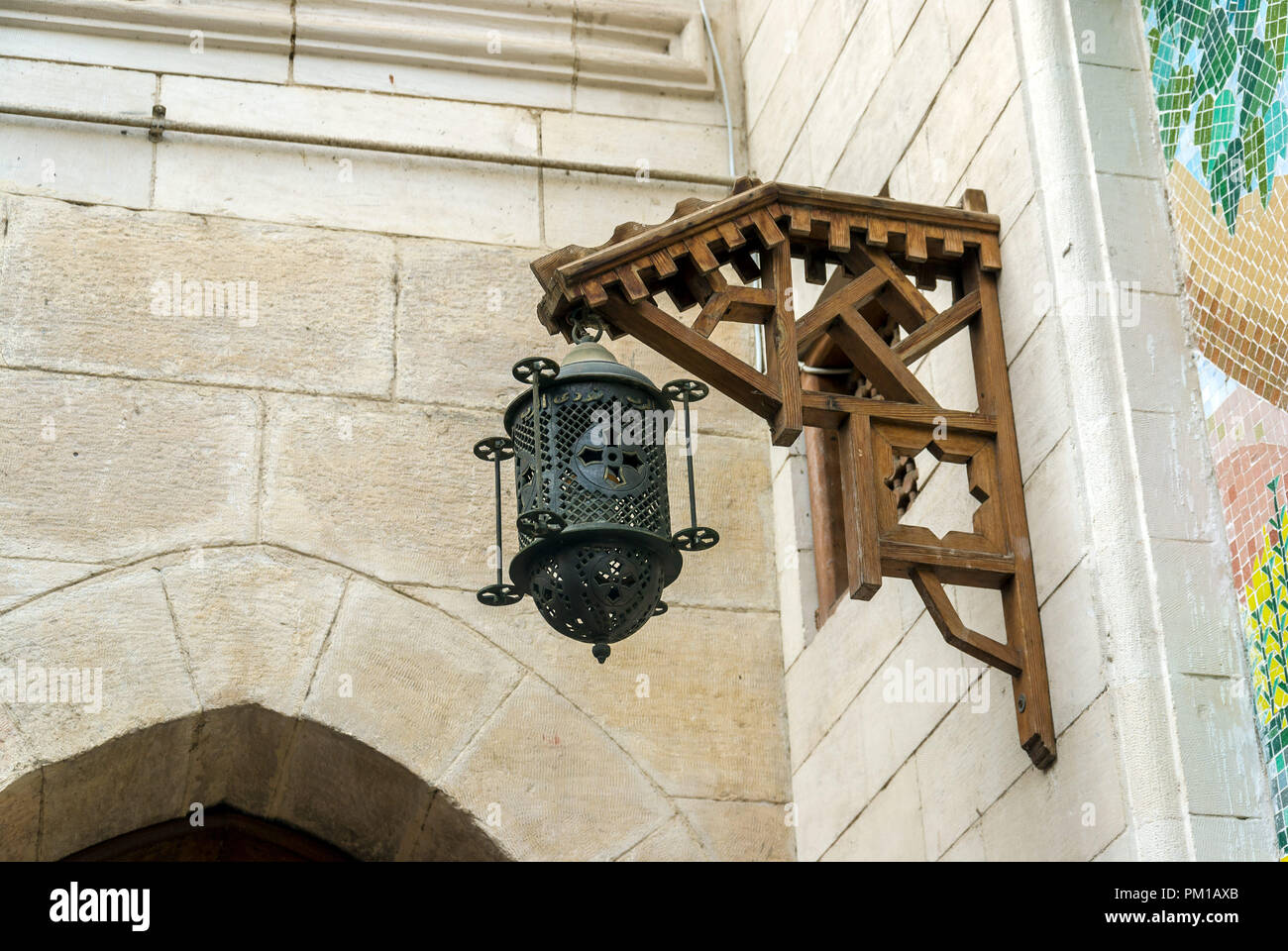 Old iron lantern with a cross hanging from a wooden frame on a stone ...