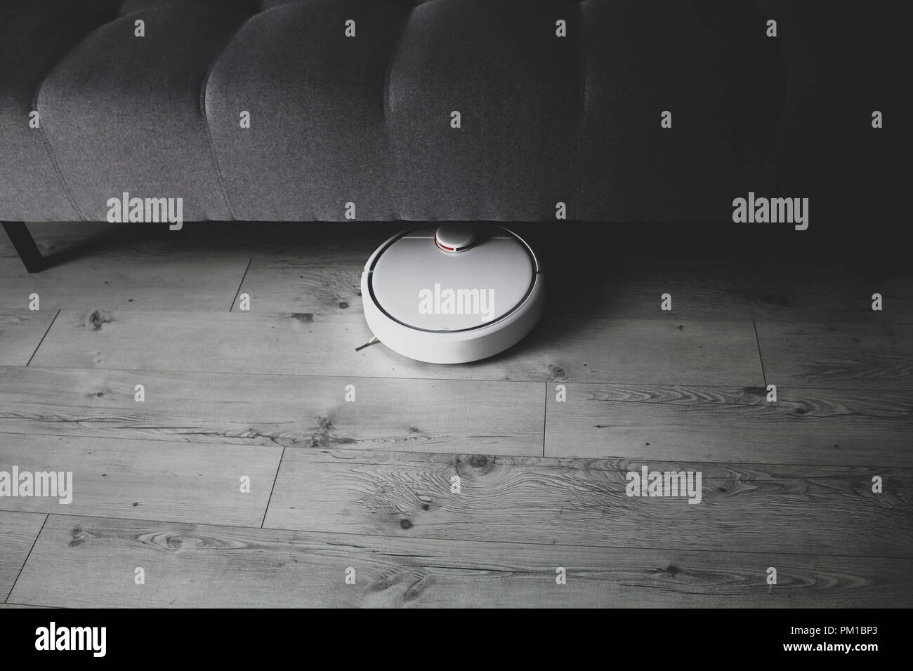 Robotic vacuum cleaner cleaning under the sofa, technological progress, matte effect technique Stock Photo