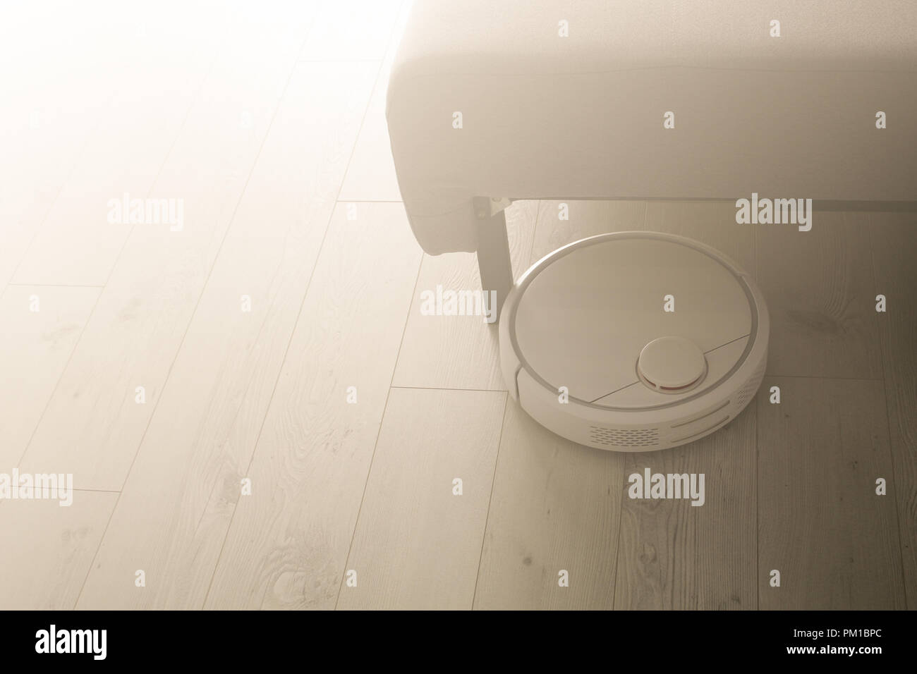 Robotic vacuum cleaner cleans the room from dust and debris, light from the window Stock Photo