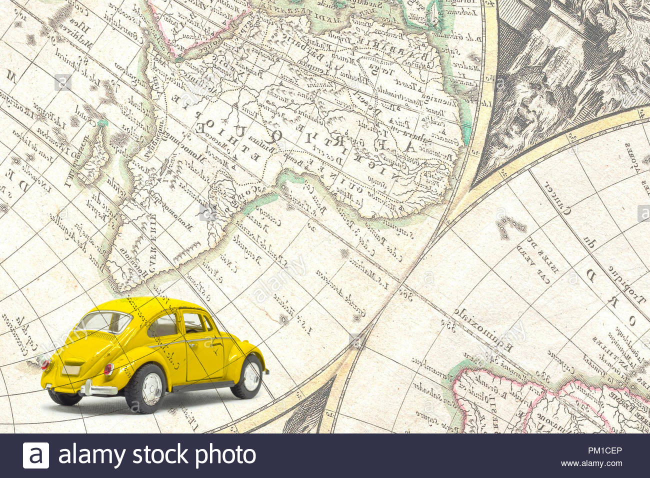 Isolated used yellow toy car, under an old map Stock Photo