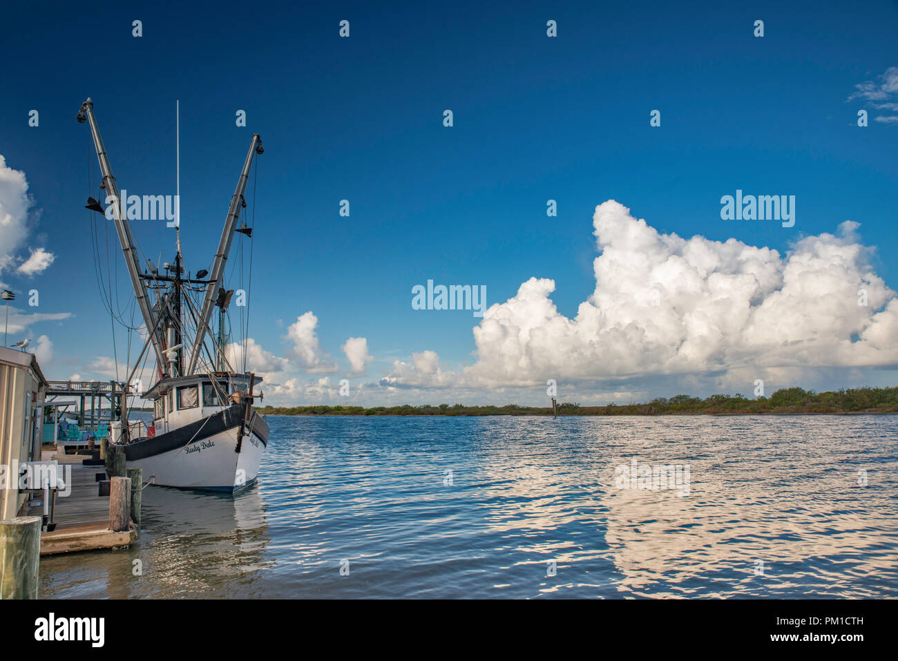 Shrimp boat at pier at Colorado River near its estuary at Gulf of Mexico, near Matagorda, Texas, USA - Stock Image