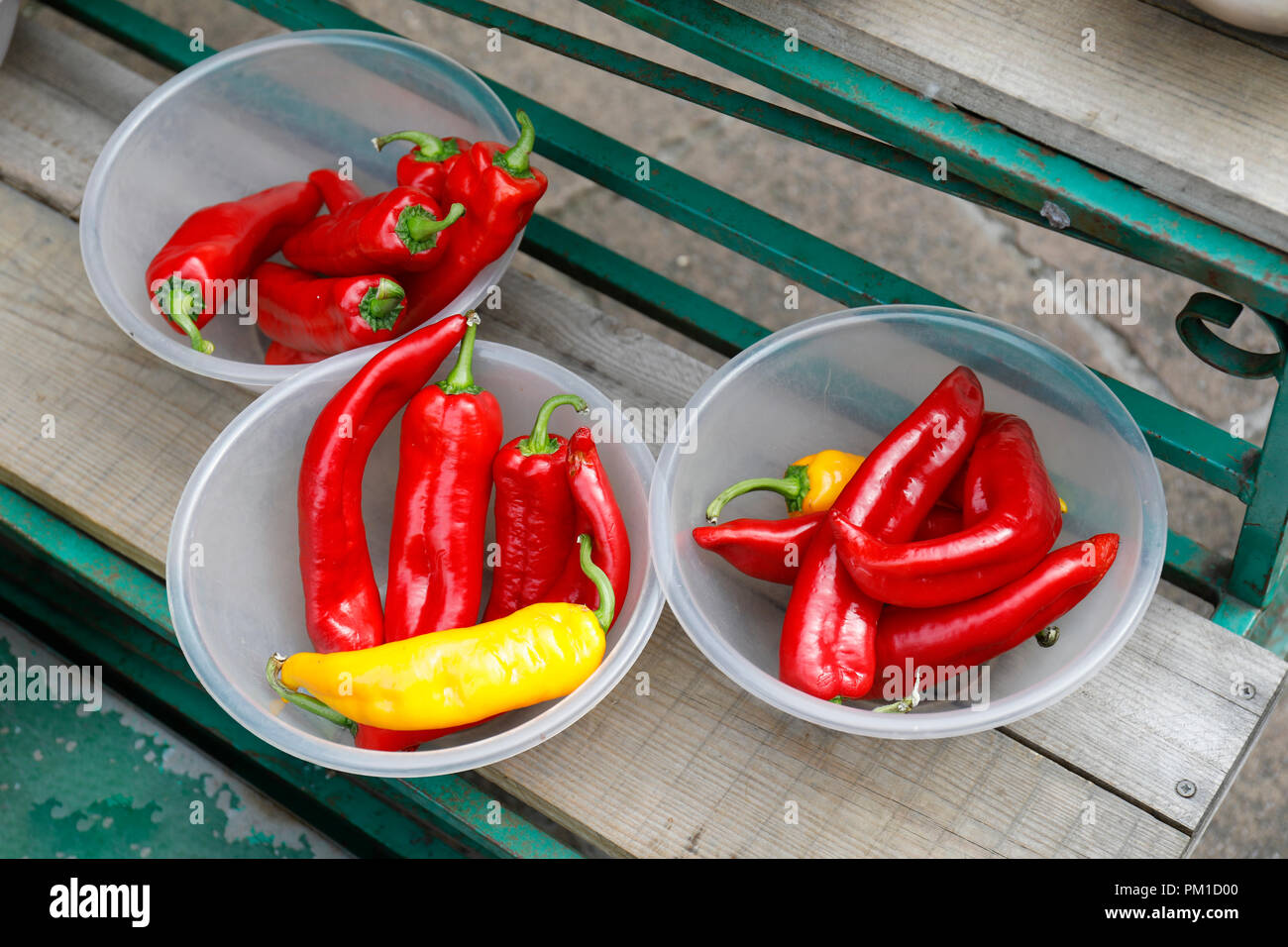 Close up of red and yellow sweet peppers in bowls outside a greengrocers for sale - Stock Image