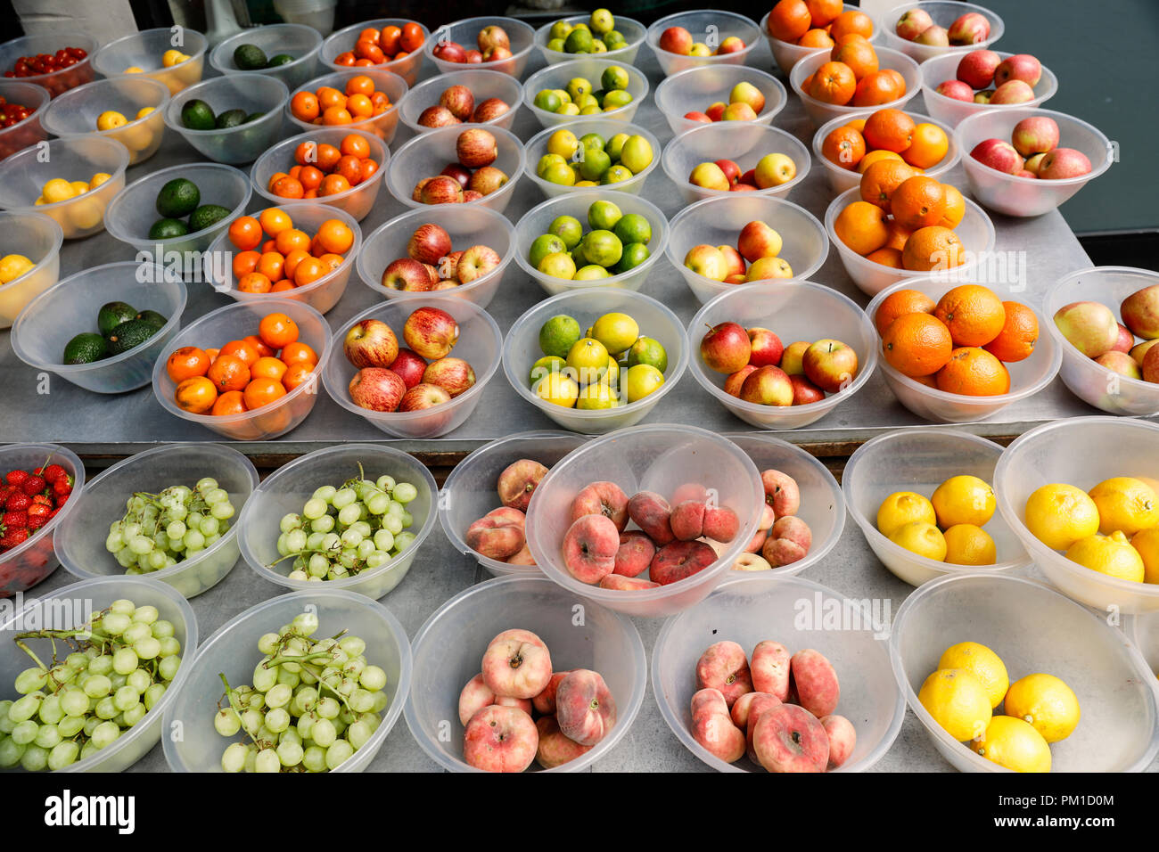 Close up of bowls of fruit displayed outside a greengrocers for sale. - Stock Image