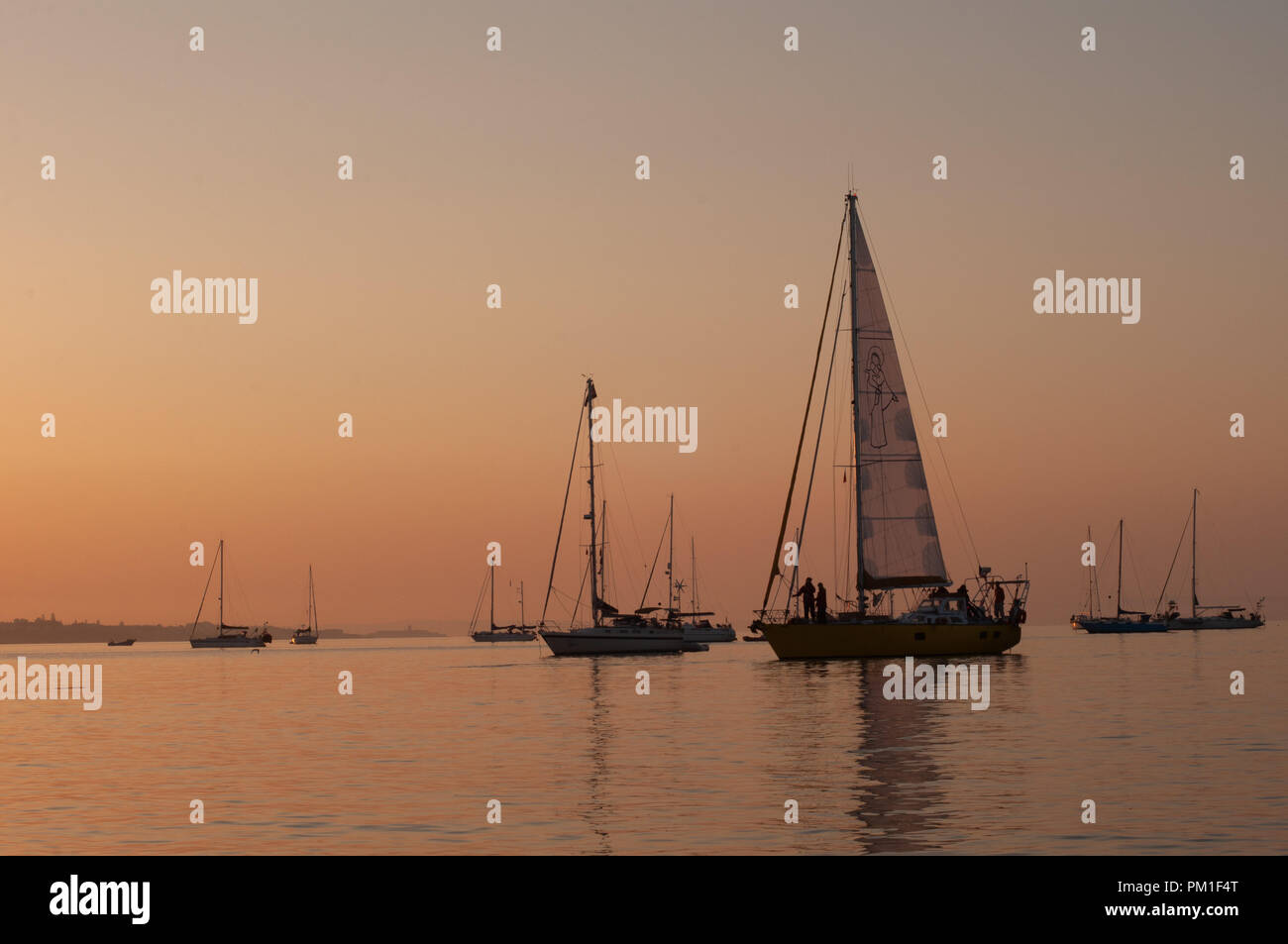 Daybreak at the Ocean with Anchored Sailing Yachts and Boats - Stock Image