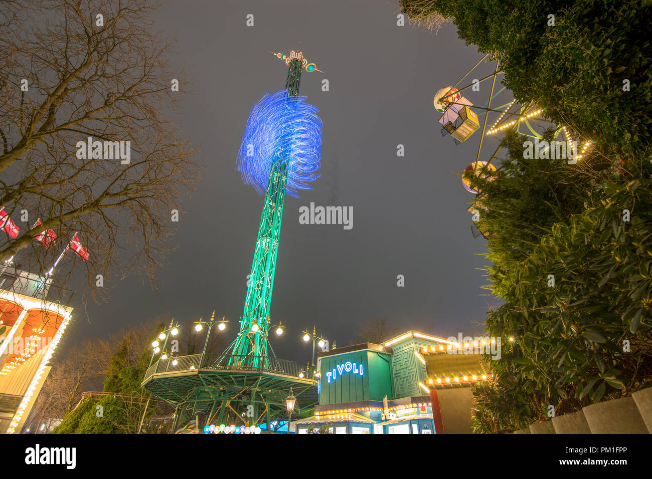 COPENHAGEN, DENMARK, MARCH 31, 2018: The The Star Flyer descends and rotates as part of it's operation next to the Ferris Wheel, and above the Little  - Stock Image
