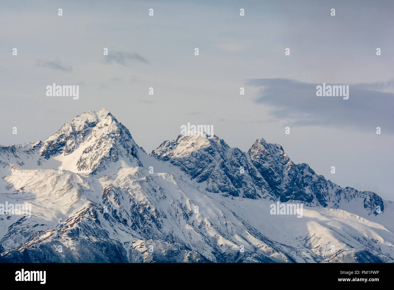 Twin and Goats peaks are dusted with snow but the solid rock still shows through - Stock Image