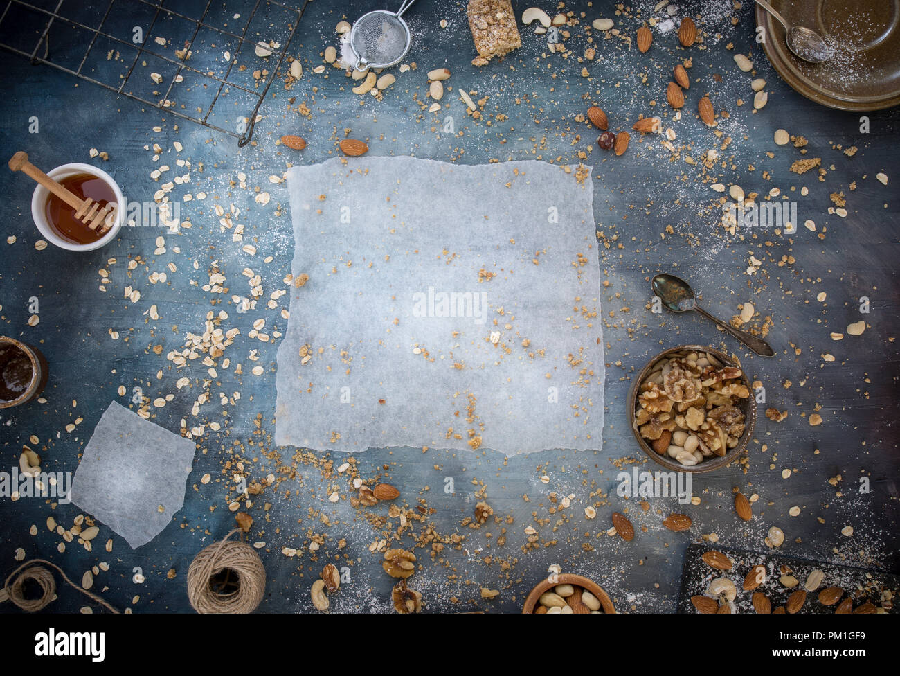 home baked caramel slices baking paper on a textured blue background with nuts seeds and grains, a flatlay overhead image, part of a series - Stock Image