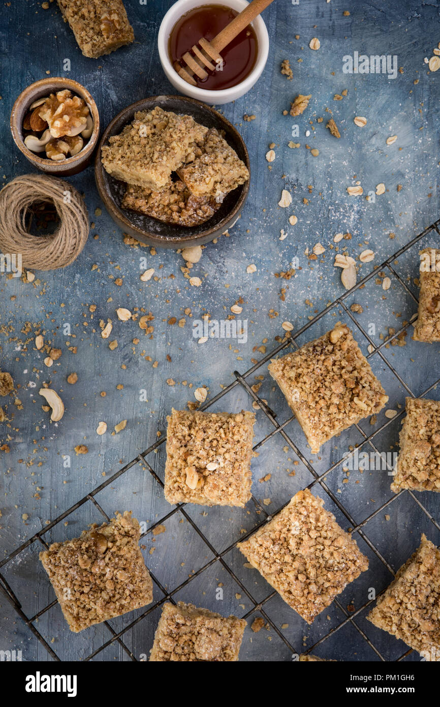 home baked caramel slices baking paper on a textured blue background with nuts seeds and grains, a flatlay overhead image - Stock Image