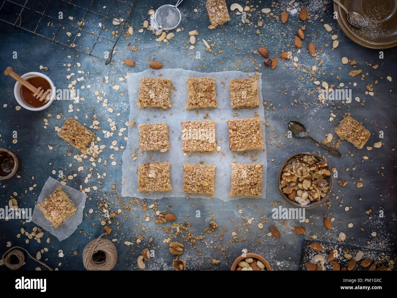 home baked caramel slices baking paper, with a textured blue background including nuts seeds and grains, a flatlay overhead image, part of a series - Stock Image