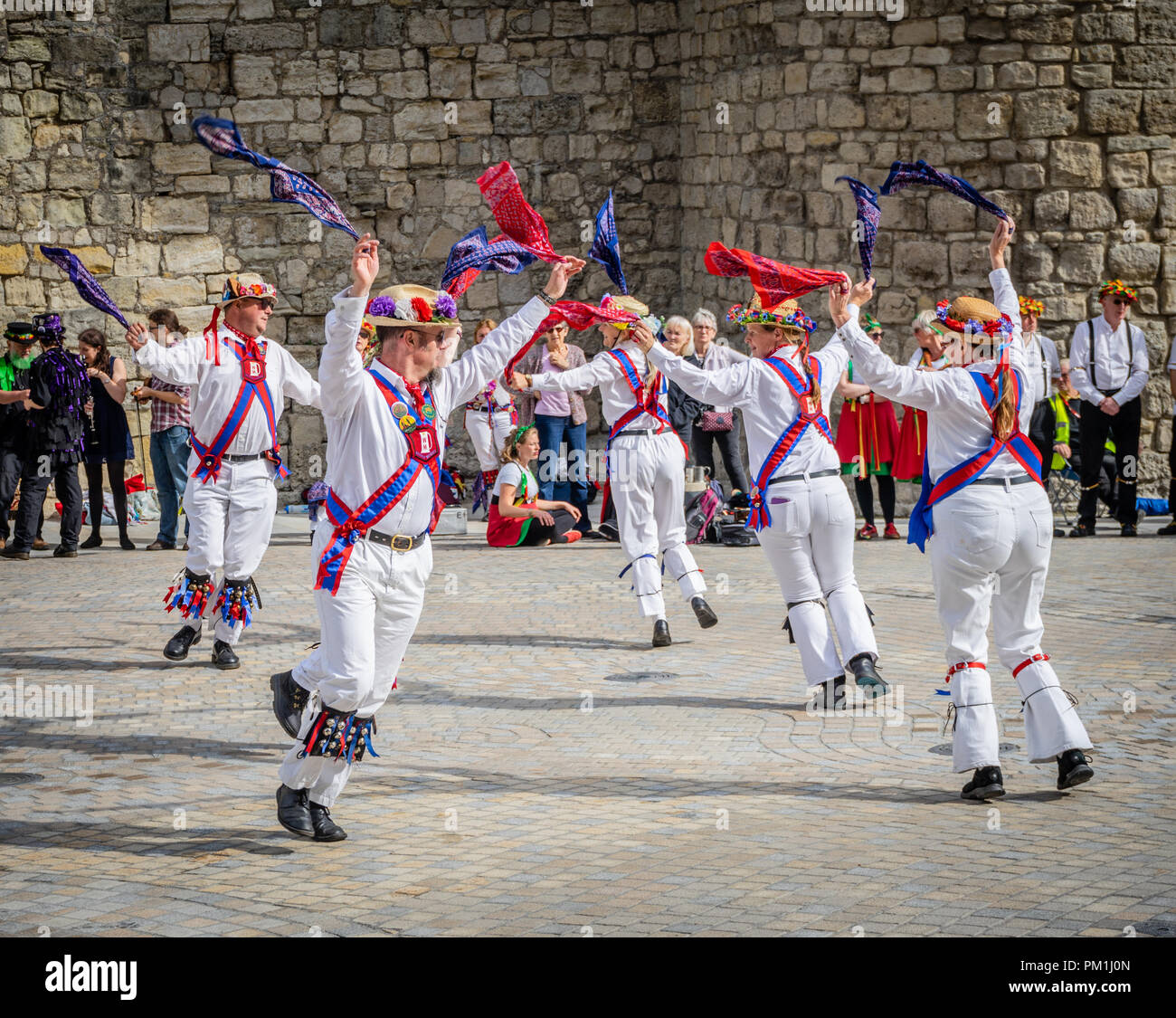 A group of female and male Morris dancers perform a Morris dance in front of the Southampton Walls, Southampton, Hampshire, England, UK - Stock Image