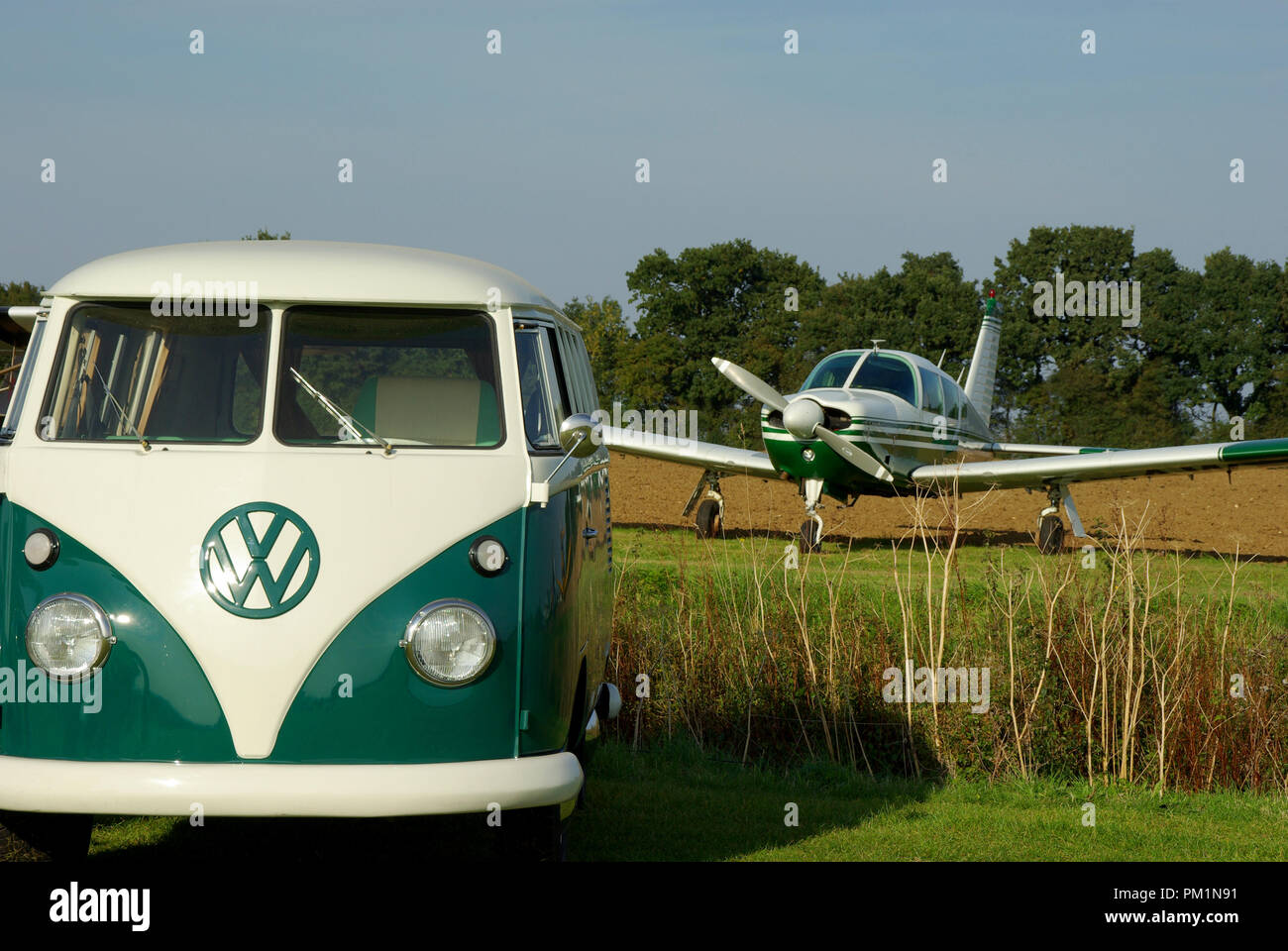 Matching coloured VW Camper van and Piper Cherokee Arrow light aircraft plane at a small field grass airfield. Classic timeless period countryside - Stock Image