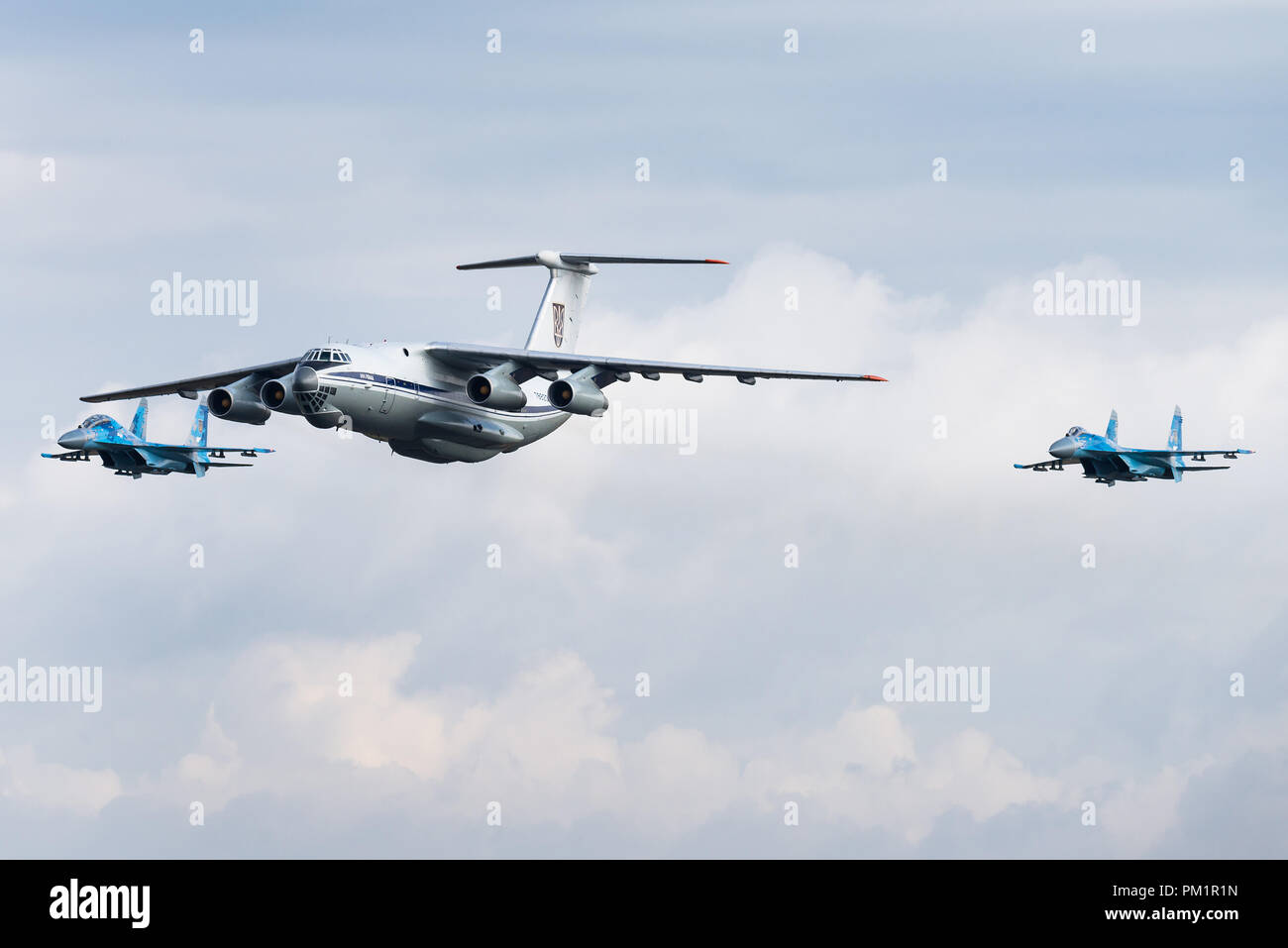 A Ilyushin Il-76 military transport aircraft of the Ukrainian Air Force is escorted by two Sukhoi Su-27 fighter jets. - Stock Image