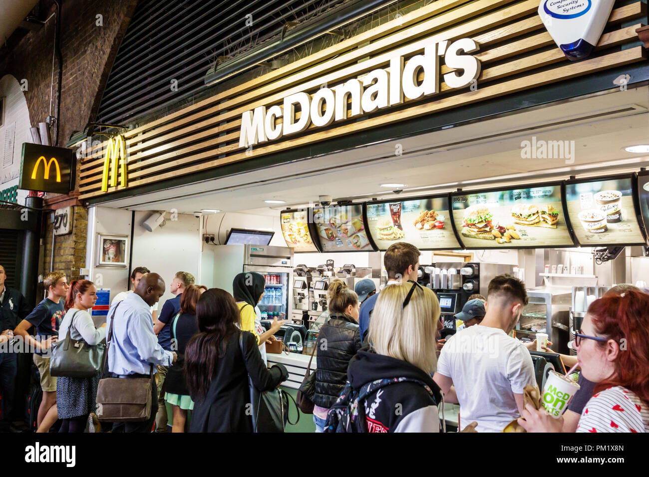 London England Great Britain United Kingdom South Bank Waterloo Station McDonald's fast food restaurant counter line queue ordering Black man woman - Stock Image