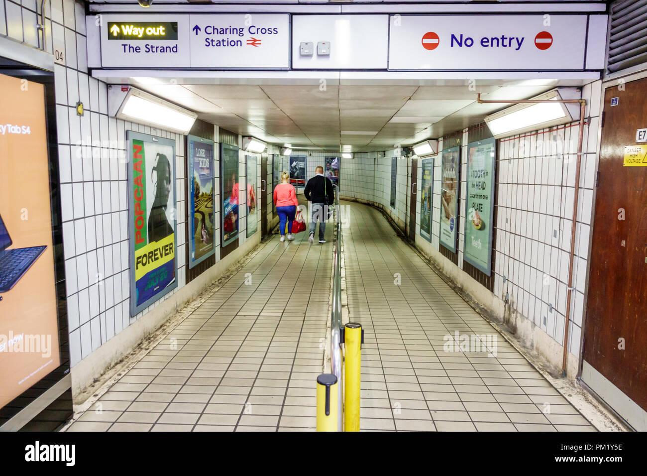 London England Great Britain United Kingdom Charing Cross Underground Station subway tube public transportation inside exit hallway sign advertisement - Stock Image