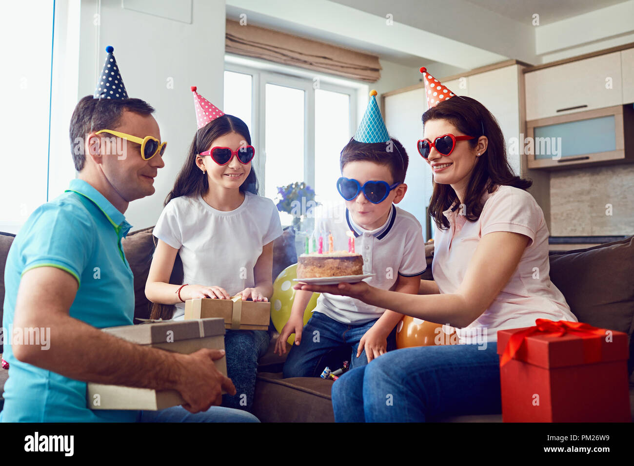 Happy Family celebrates birthday with a birthday cake - Stock Image