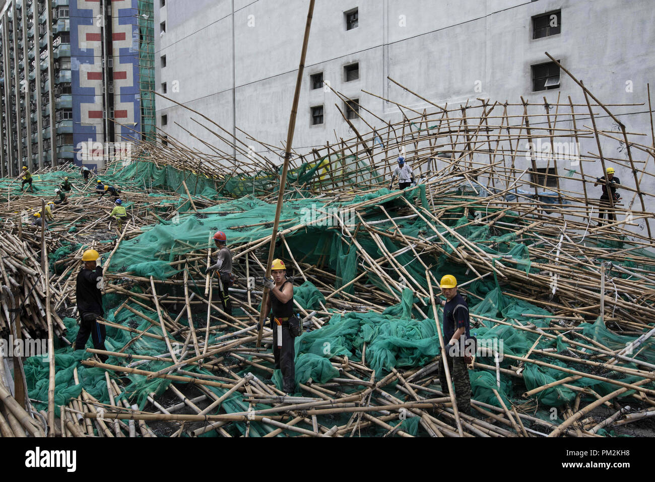 Hong Kong, Kowloon, China. 17th Sep, 2018. Workers remove bamboo scaffolding after it has collapse, fall and blocked the street. Super Typhoon Mangkhut aftermath is visible in most districts of Hong Kong.The super typhoon Mangkhut has passed next to Hong Kong on the 16th September causing large scale damages around the city, there are 432 people injured due to the storm with 2 still in critical condition. Credit: Miguel Candela/SOPA Images/ZUMA Wire/Alamy Live News - Stock Image