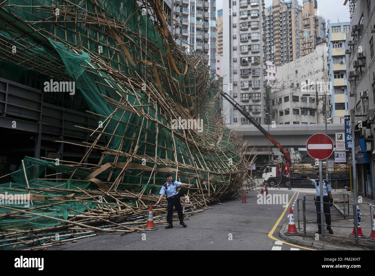 Hong Kong, Kowloon, China. 17th Sep, 2018. Police officers cut the street after bamboo scaffolding has collapsed and fall into the street. Super Typhoon Mangkhut aftermath is visible in most districts of Hong Kong.The super typhoon Mangkhut has passed next to Hong Kong on the 16th September causing large scale damages around the city, there are 432 people injured due to the storm with 2 still in critical condition. Credit: Miguel Candela/SOPA Images/ZUMA Wire/Alamy Live News - Stock Image