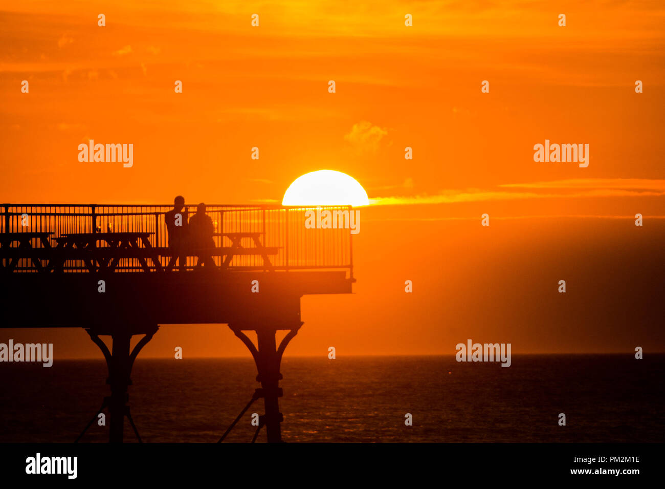 Aberystwyth Wales UK, Monday 17 September 2018  UK Weather:  People on the pier in Aberystwyth enjoying a drink in  the remarkably warm weather as they wait for Storm Helene to roll in overnight.  The west of the UK is bracing itself for the impact of Storm Helene, which is predicted to strike tonight and into tomorrow morning, with winds gusting up to 70mph in exposed areas and the risk of danger to life from flying debris   Photo © Keith Morris / Alamy Live News - Stock Image