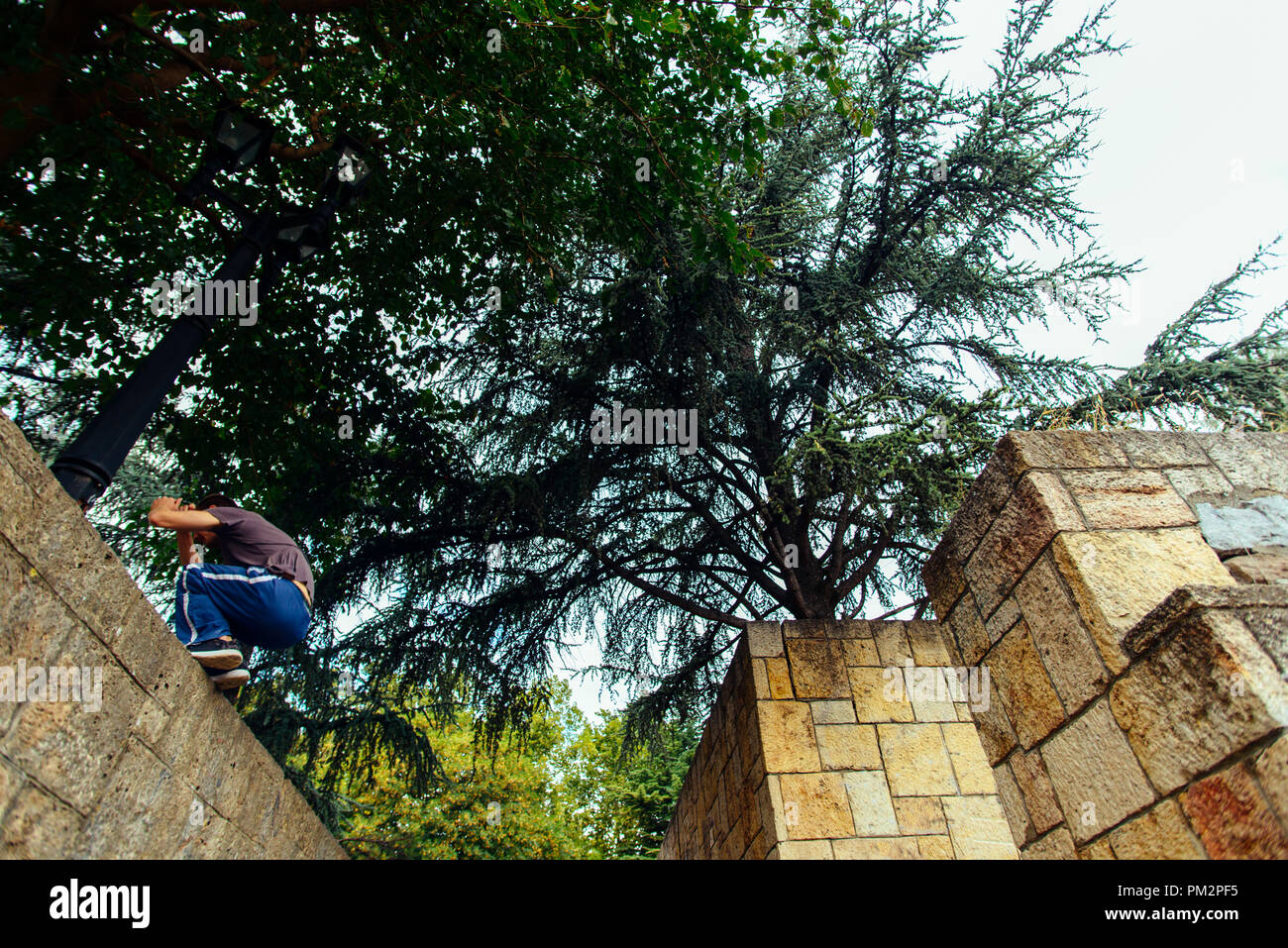 Parkour man exercising while jumping of the wall - Stock Image