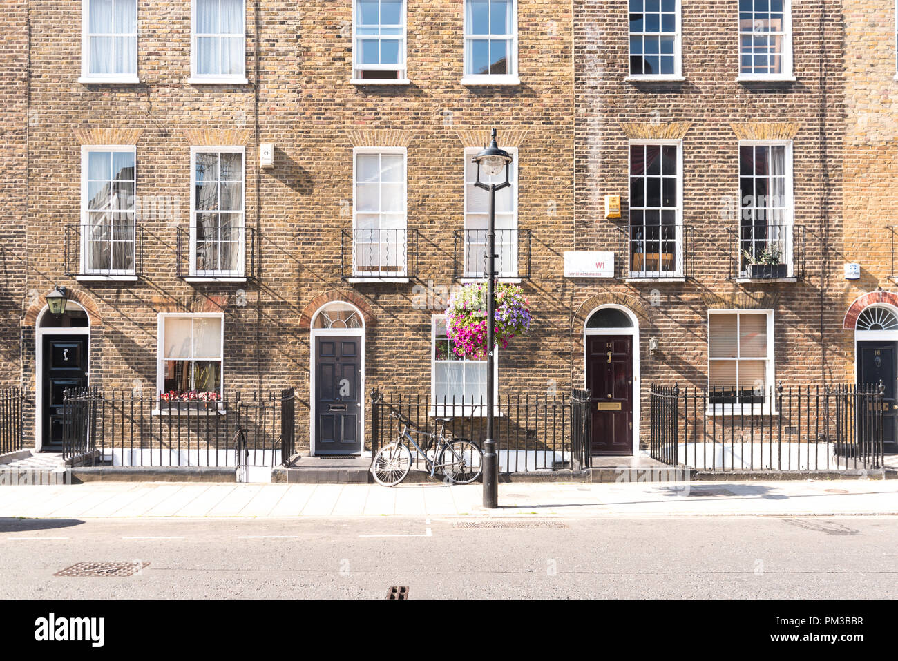 Front facades and arched doors of historic brick London Terrace houses with tall windows and iron railing out front with a bicycle on the sidewalk and - Stock Image