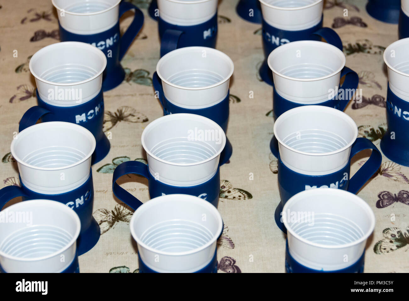 Rows of plastic cups in holders - Stock Image