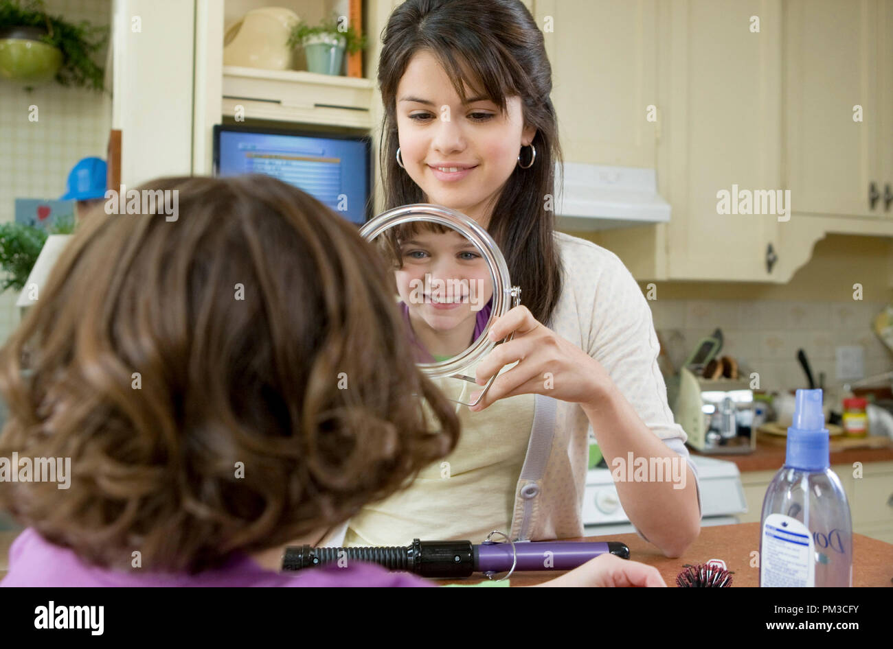 Beezus Quimby (Selena Gomez, standing) and younger sister Ramona (Joey King) enjoy a rare moment of family tranquility in Ramona and Beezus. - Stock Image