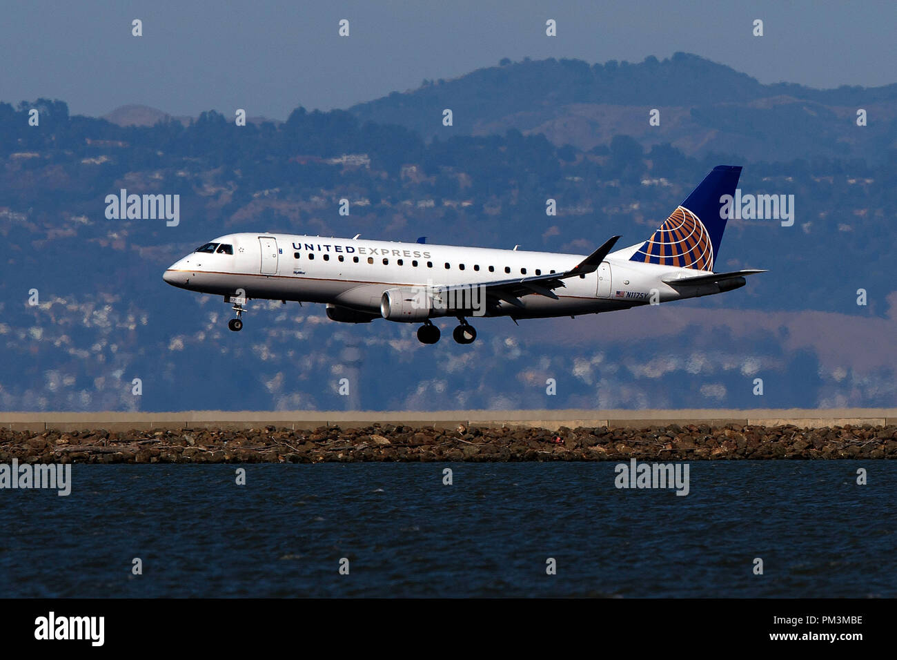 Embraer ERJ-175LR (N117SY) operated by SkyWest Airlines for United Express landing at San Francisco International Airport (KSFO), San Francisco, California, United States of America - Stock Image