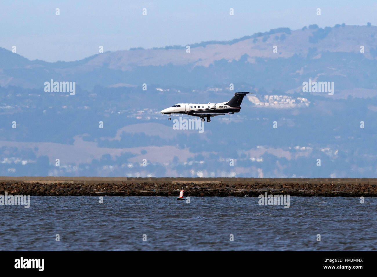 Embraer Phenom 300 (N361FX) landing at San Francisco International Airport (KSFO), San Francisco, California, United States of America - Stock Image