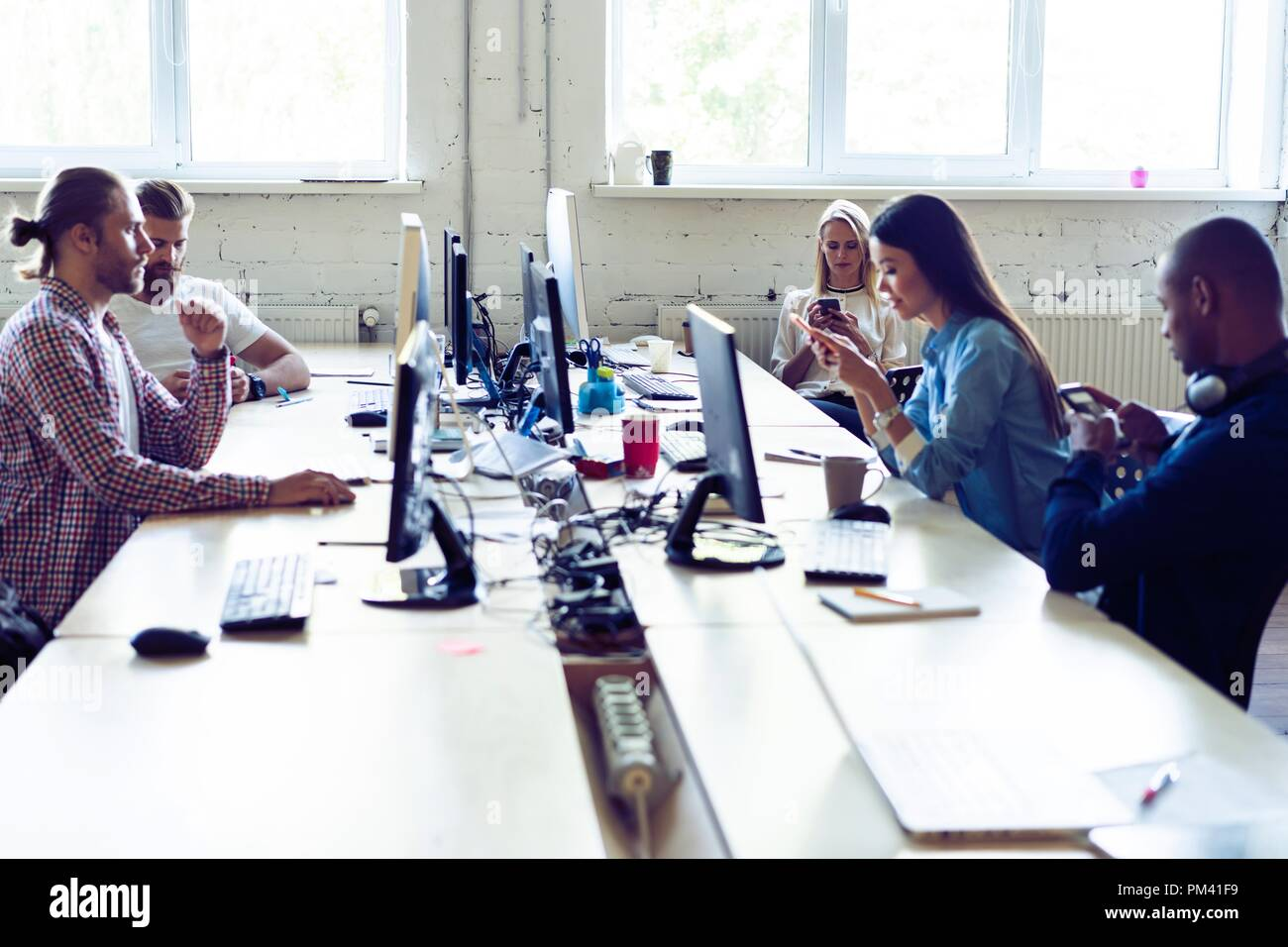 Just working day. Young modern colleagues in smart casual wear working together while spending time in the creative office. - Stock Image