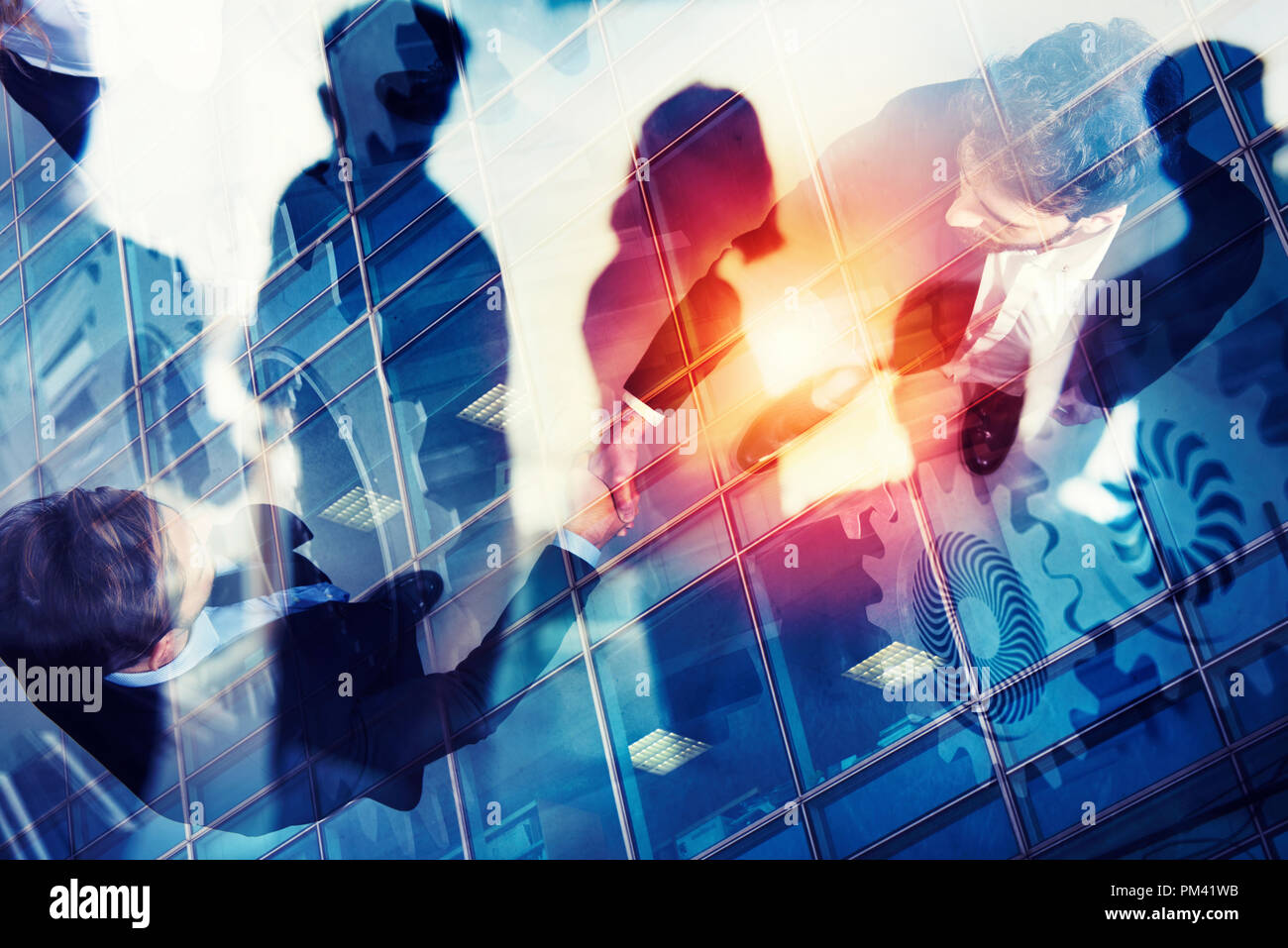 Handshaking business person in office. concept of teamwork and partnership. double exposure with gears system and network effects - Stock Image