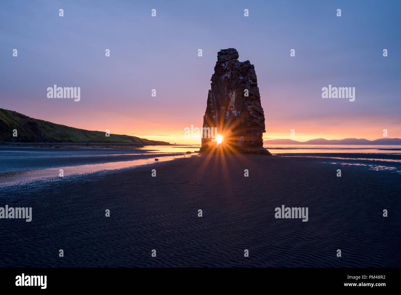 Hvitserkur - basalt stack on the shore of ocean, Vatnsnes peninsula, Iceland. Tourist attraction. Rays of the Rising Sun Stock Photo