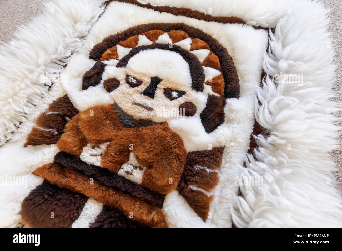Typical Andean craftsmanship and souvenir: a soft fluffy patchwork rug hand crafted from pieces of alpaca skin to form a picture of a pre-Inca figure - Stock Image