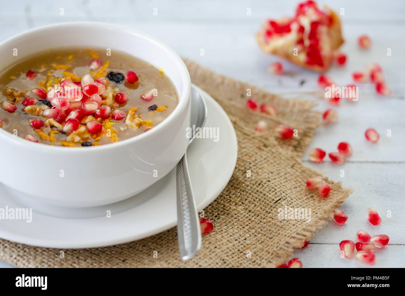 Noah's pudding in white bowl. The dried fruits, legumes and cereals are made with wheat and sugar. It is decorated with walnut, dried fruit and pomegr - Stock Image