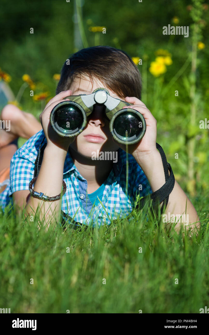 Boy young researcher exploring with binoculars environment in green garden - Stock Image
