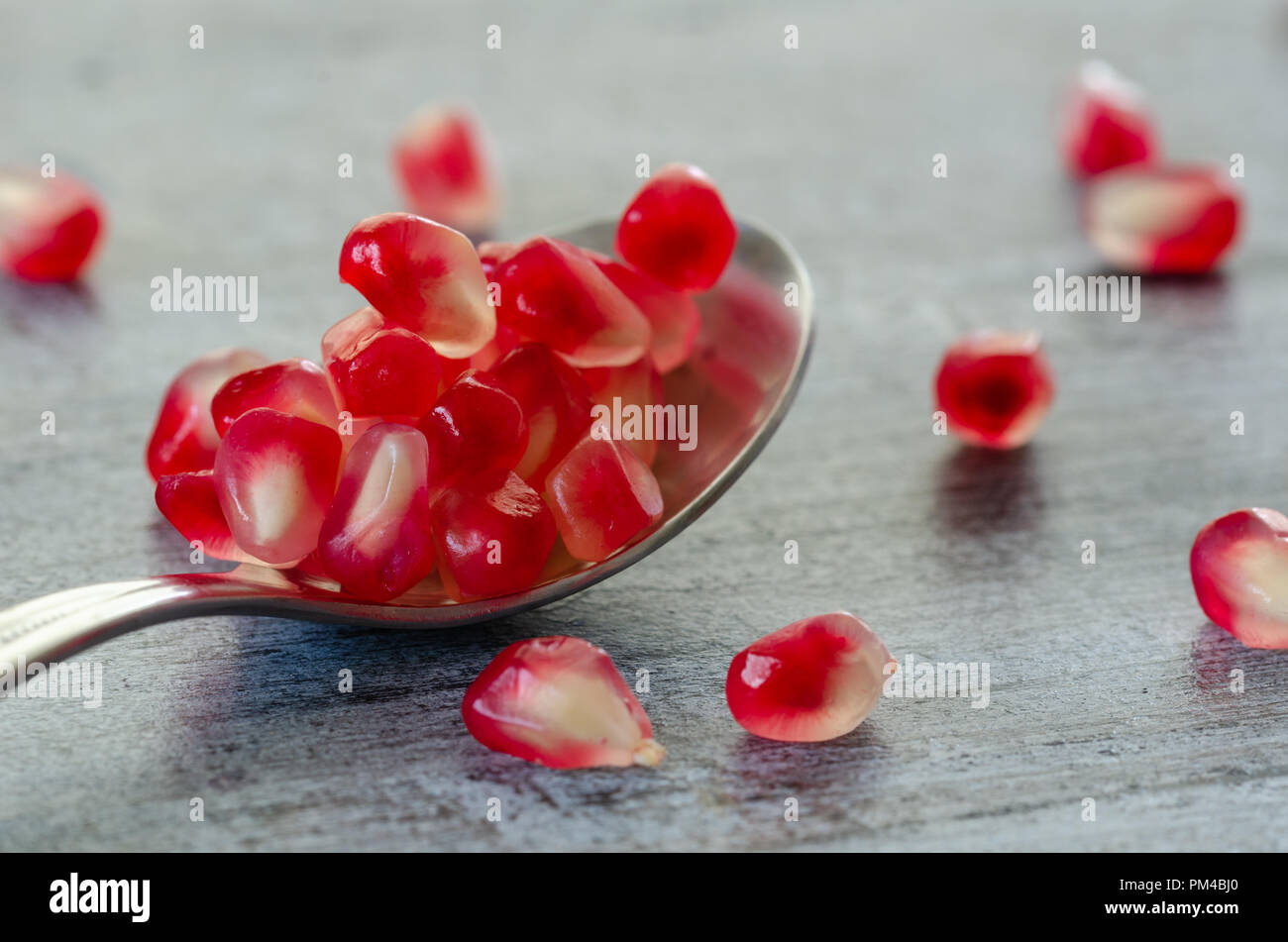 Pomegranate seeds are in spoon on wooden table. Close up,detail. - Stock Image